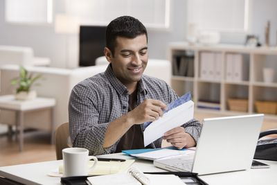 Man opening mail in home office