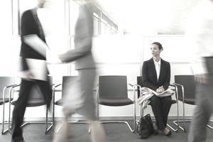 Job applicant sitting in busy waiting area waiting on a chance to interview.