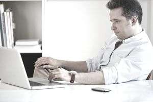 A frustrated man at a desk with a laptop