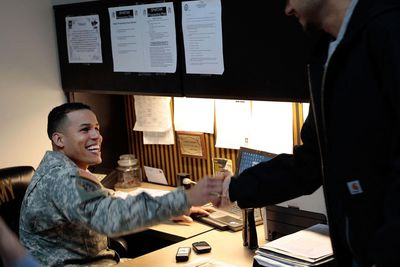 Army recruiter Staff Sgt. Pablo Valdez Martinez (L) smiles as he greets a potential Army recruit in the new office for the City Hall Recruiting Station December 17, 2009 in lower Manhattan in New York.