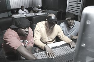 Hip-hop music artists working on their music with a sound board in a studio