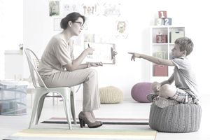 Woman conducting a psychological test with a young boy in a clinical setting