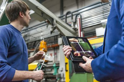 Factory worker and supervisor checking product quality with tablet