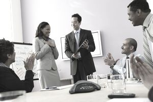 Woman receiving a promotion in business meeting