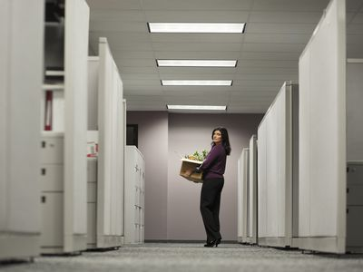 Woman leaving office with a box of her things after her job was terminated