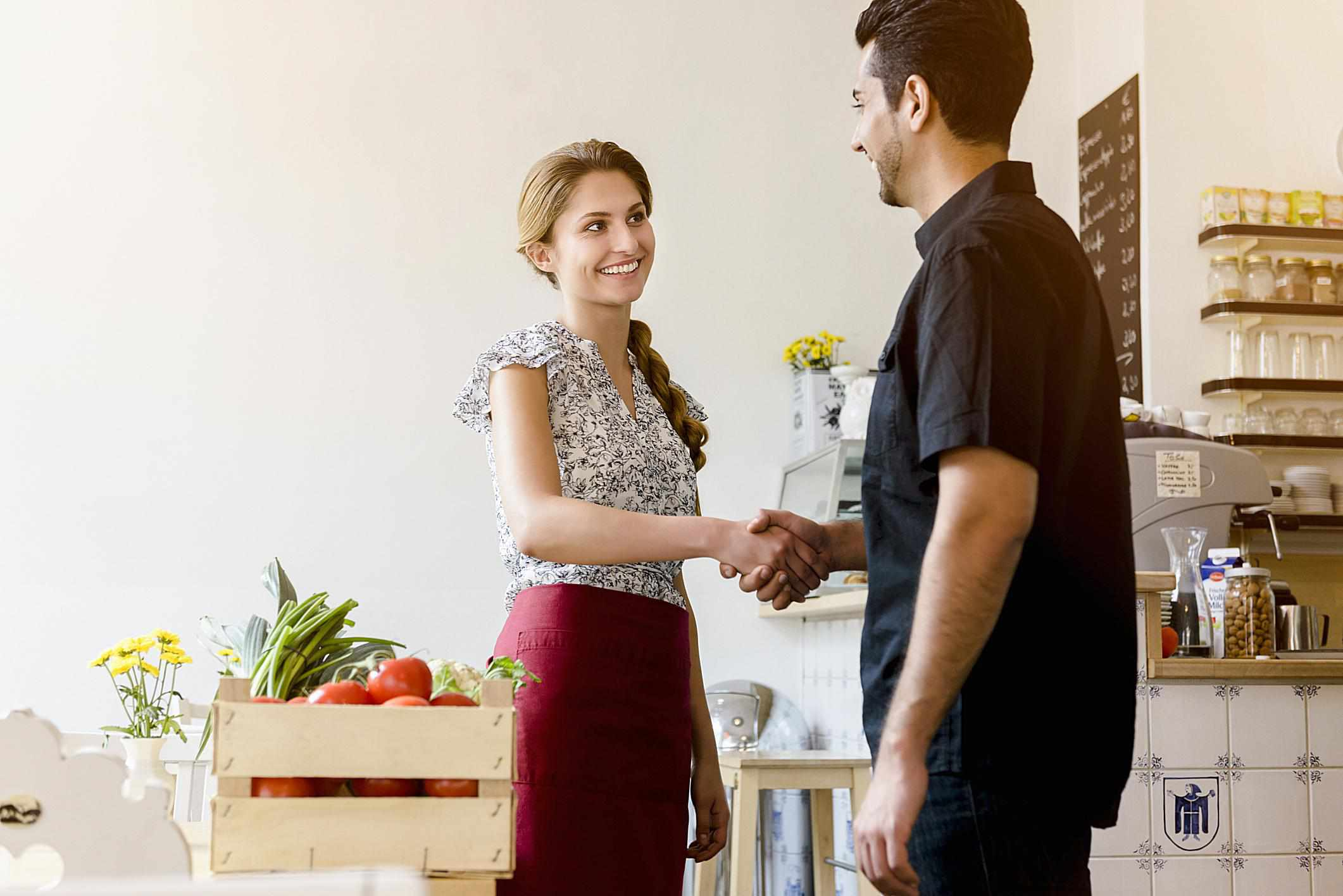 A man and a woman shaking hands in a cafe.
