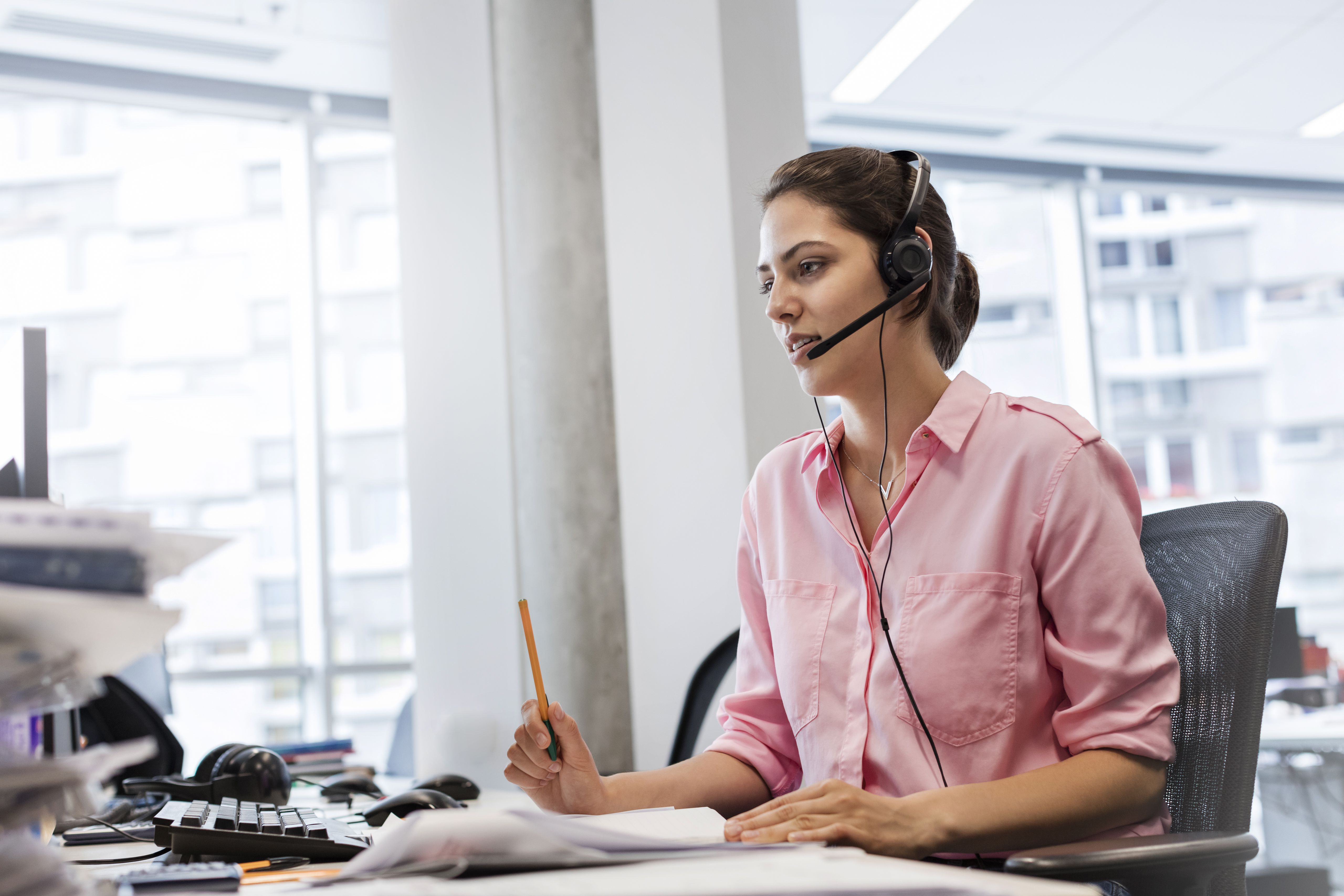 Woman with hands-free device talking on telephone in call center