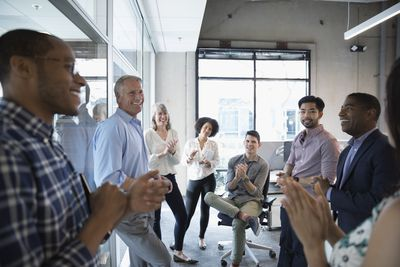 A diversified group of male and female employees clapping during a stand-up team meeting.