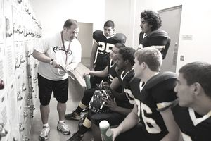 Coach talking to football players in locker room