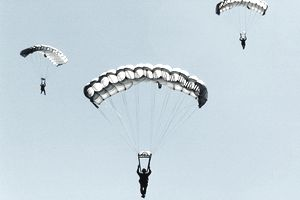 Sailors and airmen parachuting during a training exercise.