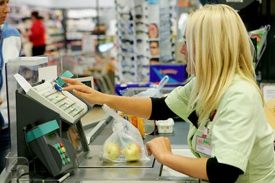 An hourly employee rings a customer up at a register
