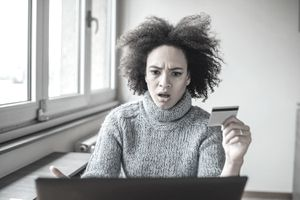 Woman Using Laptop and Credit Card, Having Serious Face Expression