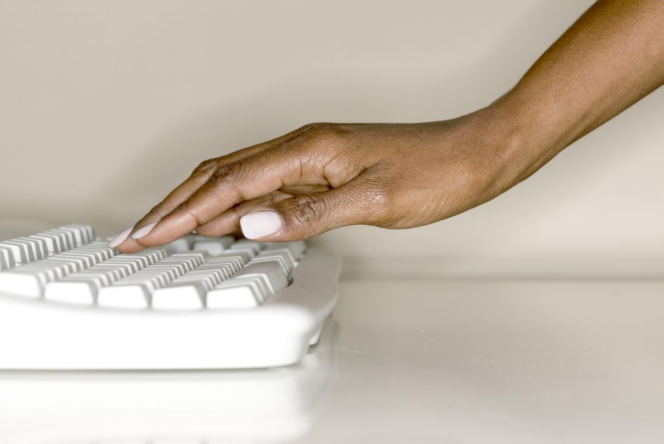 A woman's hand on computer keyboard