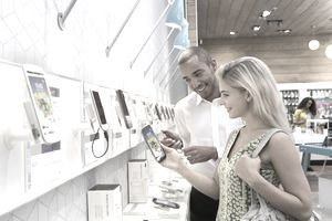 Store manager assisting customer in phone store