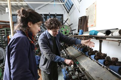 Weaver showing apprentice how to use cone winder