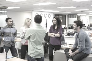 group of employees in an office building standing in a circle chatting