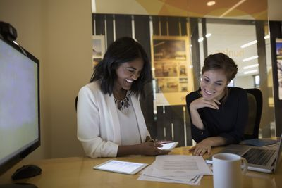 Two coworkers writing a reference letter for an employee