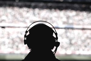 sports caster silhouette in front of crowd at sports game