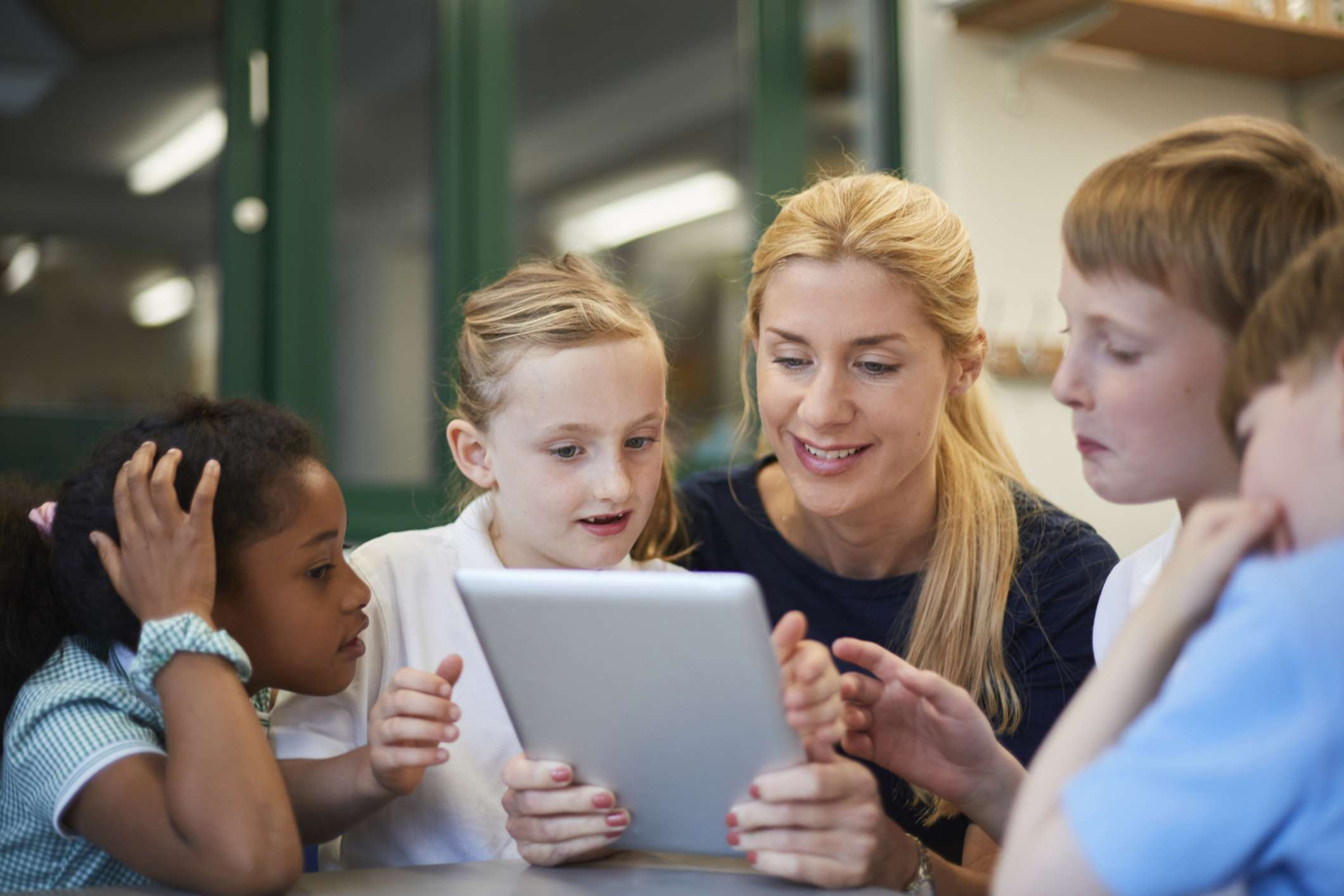 Substitute teacher reading from tablet to schoolboys and girls in classroom
