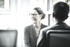 Laughing mature businesswoman in team meeting