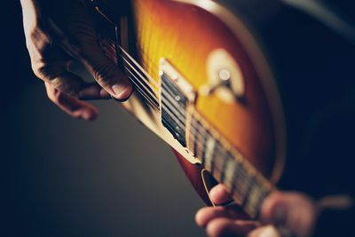 Close up of a session player fingerpicking a guitar.