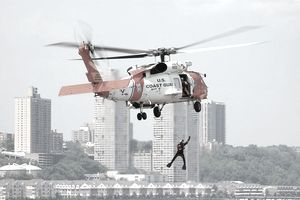 NEW YORK - MAY 27: In this handout image provided by the U.S. Coast Guard, a Coast Guard rescue swimmer hangs from a HH-60 Jayhawk helicopter, from Air Station Cape Cod, while performing a search and rescue demonstration for people enjoying Fleet Week festivities at the Intrepid Air and Space Museum May 27, 2006 in New York City. The week-long event offers parades, military demonstrations, and public tours of the participating vessels.