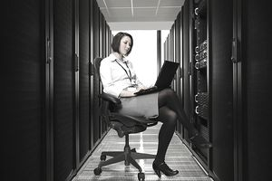 a woman working on a laptop in a server room