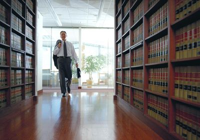 Older lawyer with briefcase entering a law library