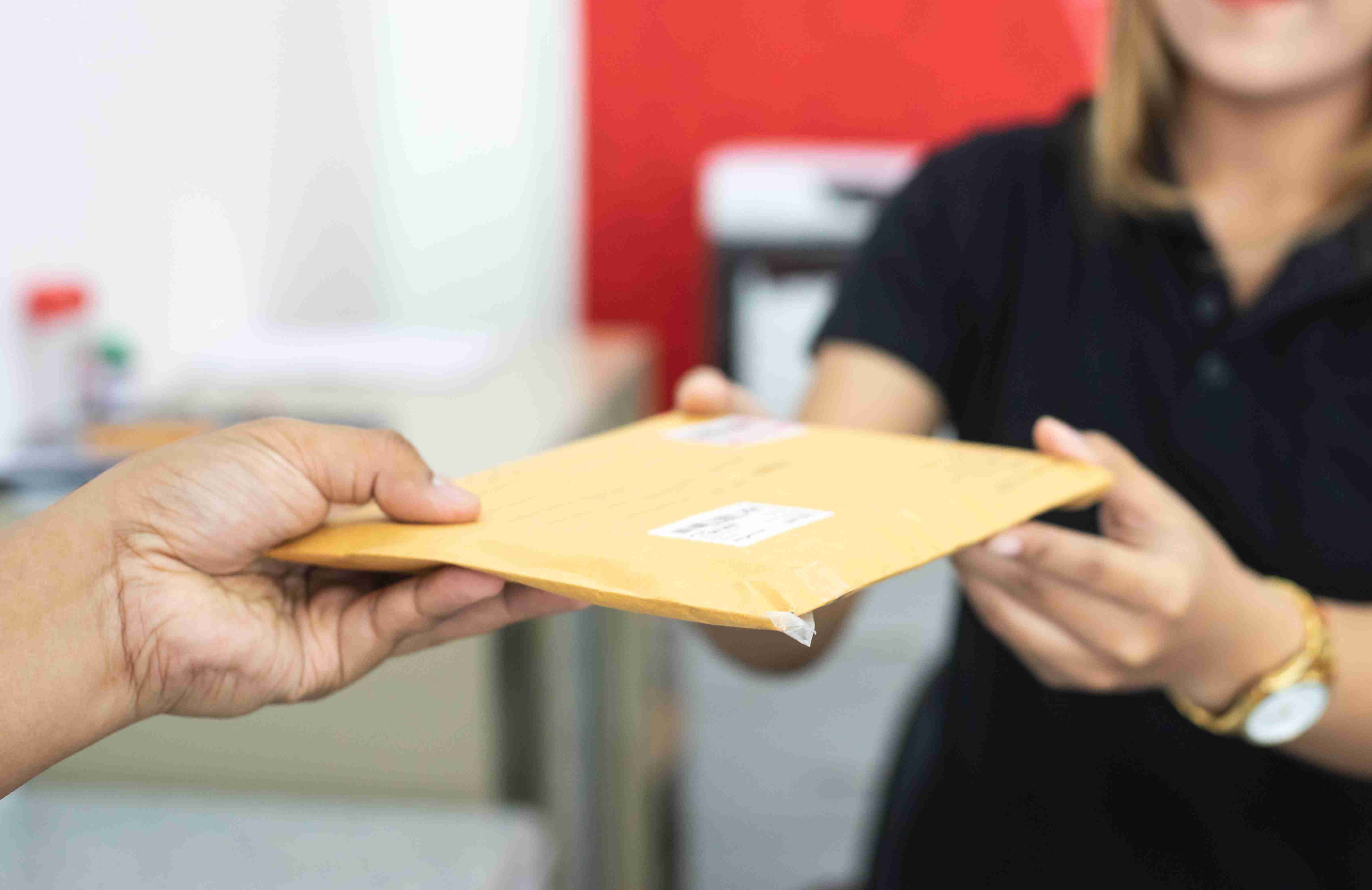 Male hand send mail envelope to the female of post office before sending