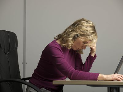 Woman at desk, head bowed over computer, as she grapples alone with illegal retaliation in her workplace