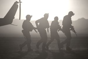 Silhouetted soldiers carrying weapons moving away from helicopter while on deployment in a dessert environment.
