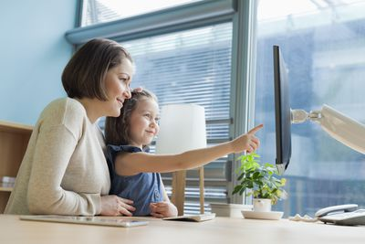 Mother and daughter looking at work desk computer on Take Your Child to Work Day.