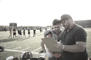 Coach and teenage boy high school football player reviewing game plan on clipboard