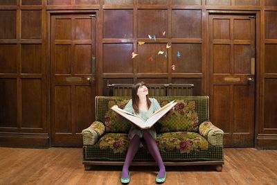 A teenage girl reading a large book