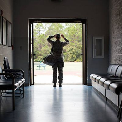 Female Air Force soldier carrying duffel bag standing in entrance of dorm