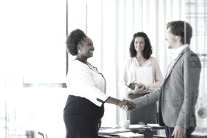 Two businesspeople shaking hands in an office.