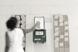 A woman in a hurry punches in at the company time clock.
