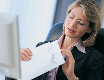 Businesswoman opens resignation letter from an employee