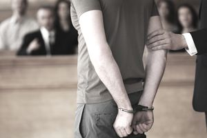 Handcuffed man standing in courtroom facing the criminal justice system