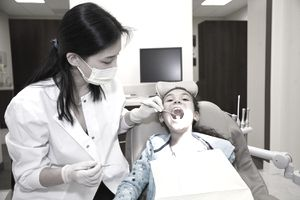Pediatric dentist examining a young patient's teeth in a dental office setting.