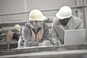 Construction worker and architect using laptop