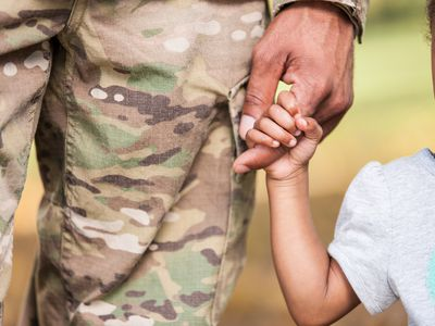 military dad holding daughter's hand