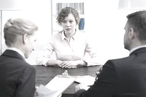 Stressed young girl talking to recruiters reviewing her background check information.
