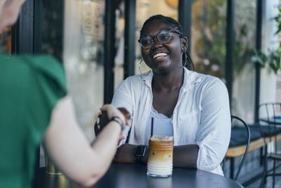 Black woman smiling and shaking hands during job interview.