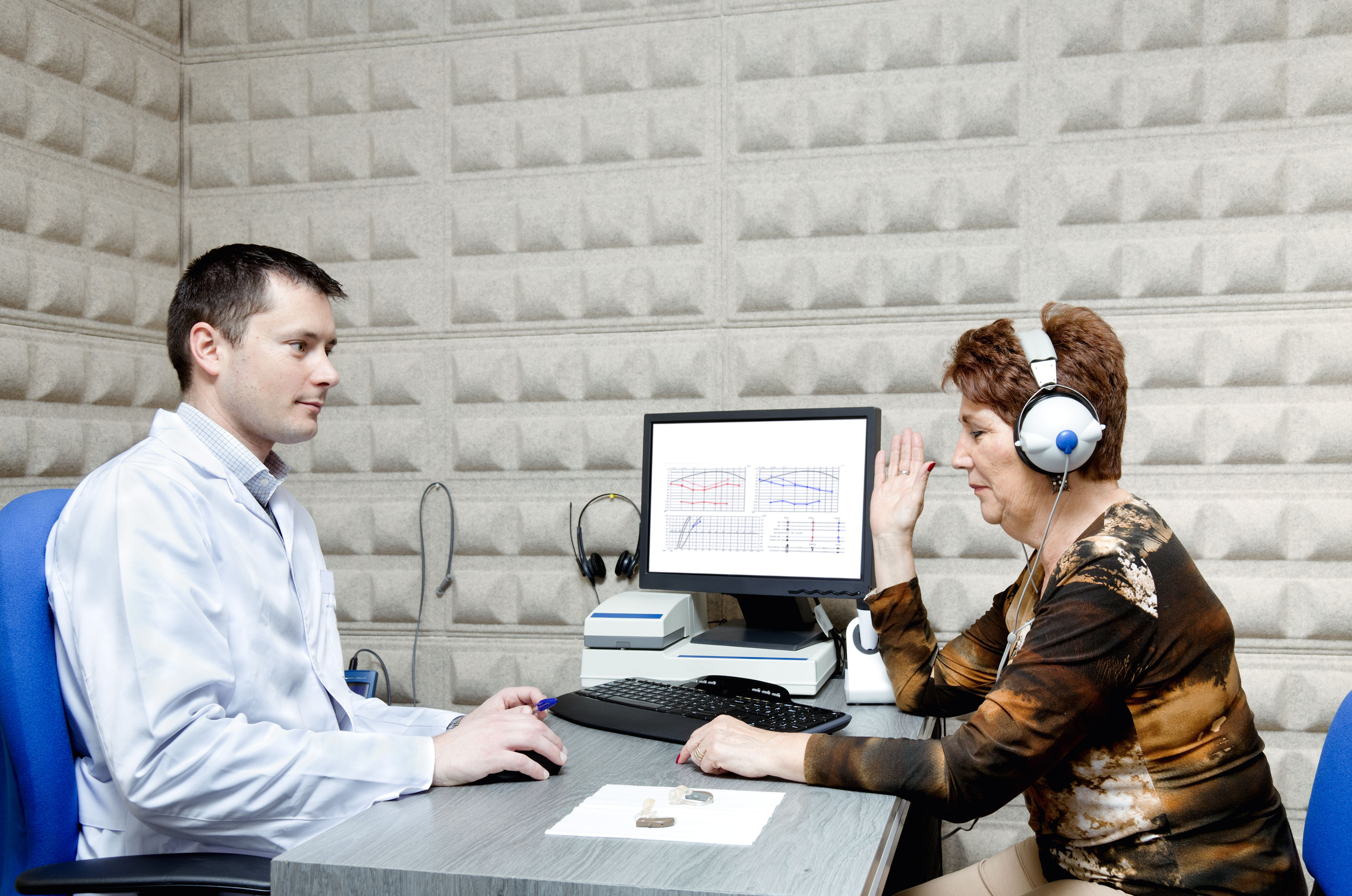 Hearing aid specialists administers a hearing test