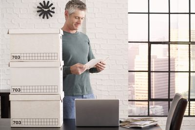 A fed-up lawyer packing up his office with boxes of files and a stack of bills on his desk.
