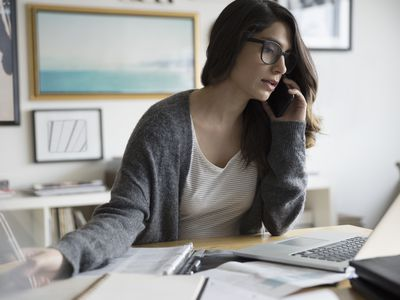 Woman working from a home office at night talking on the phone as a customer service representative.