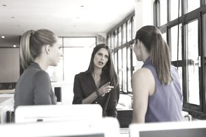 Three women in an office having an argument
