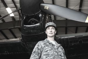 Portrait confident female army pilot standing below airplane in airplane hangar