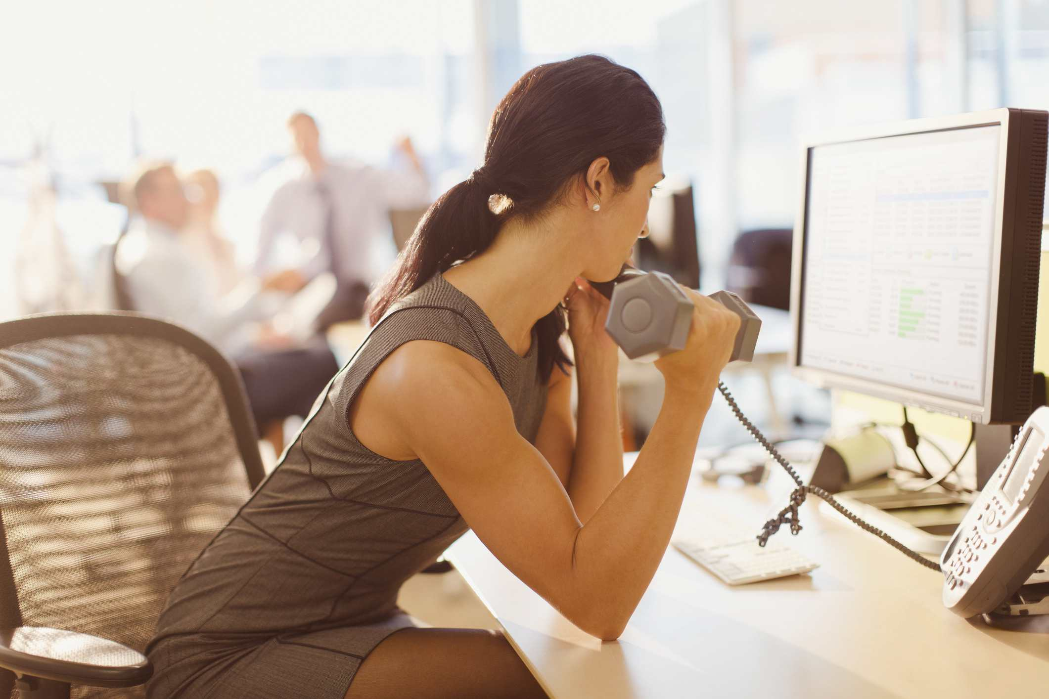Businesswoman doing biceps curls with dumbbell and talking on telephone at computer in office